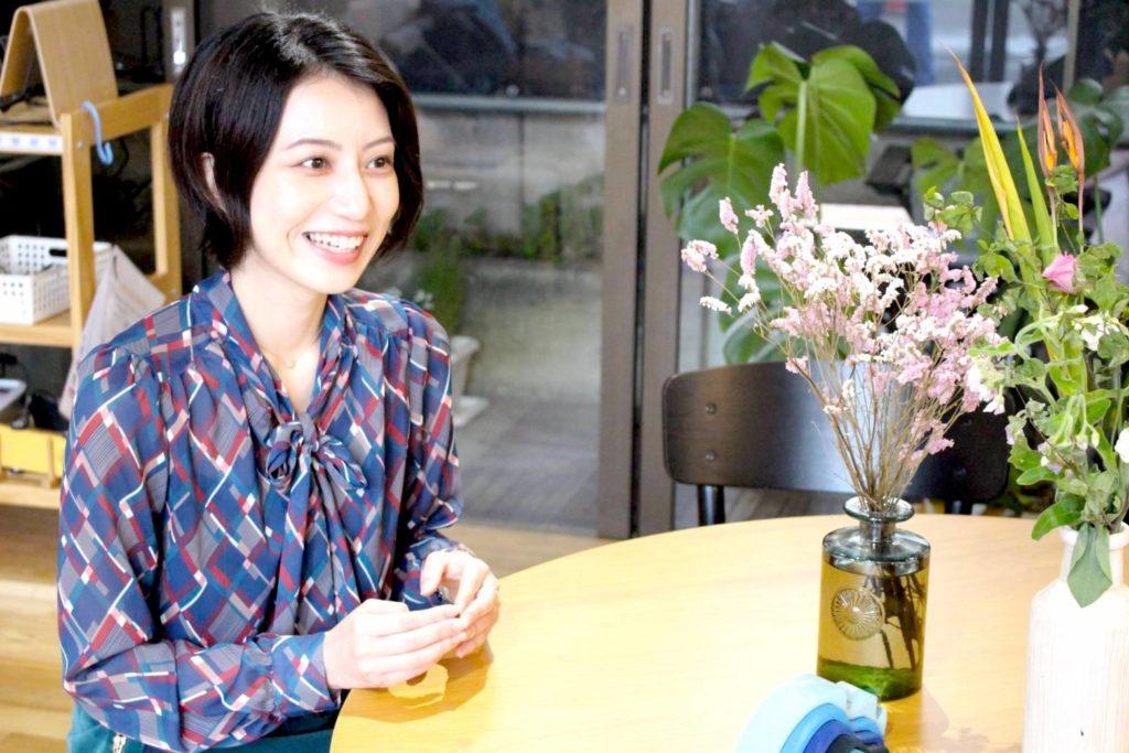 インターンシップ生の齊藤さんにインタビュー中の写真(笑顔ver)